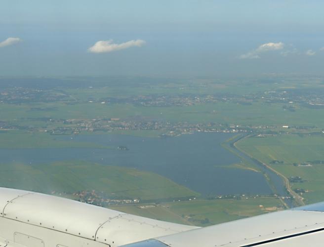 Z letadla Do Amsterdamu se kochám pohledy na rovinaté holandské pobřeží se spoustou kanálů.