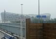 V Pekingu poté, co jsem vylezl z metra na stanici Olympic sports center. V pozadí je olympijský stadion Bird's nest (Ptačí hnízdo), v popředí plot okolo olympijského areálu. Poblíž se nacházela i bezpečnostní kontrola před vstupem do areálu. Tehdy jsem si myslel, že se tam i platí, a tak jsem olympijský areál obcházel.