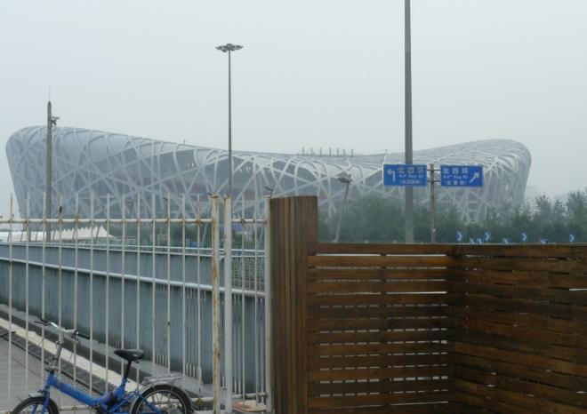 V Pekingu poté, co jsem vylezl z metra na stanici Olympic sports center. V pozadí je olympijský stadion Bird's nest (Ptačí hnízdo), v popředí plot okolo olympijského areálu. Poblíž se nacházela i bezpečnostní kontrola před vstupem do areálu. Tehdy jsem si mylně myslel, že se tam platí za vstup, a tak jsem olympijský areál zbytečně obcházel podél rušných silnic.