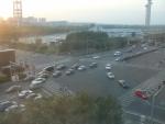 Křižovatka pod hotelem trochu ilustruje divokost tamní dopravy. Na přechodu už přecházejí lidé, přesto proud aut stále ještě dojíždí. V pozadí vlevo je rozhledna v olympijském areálu.