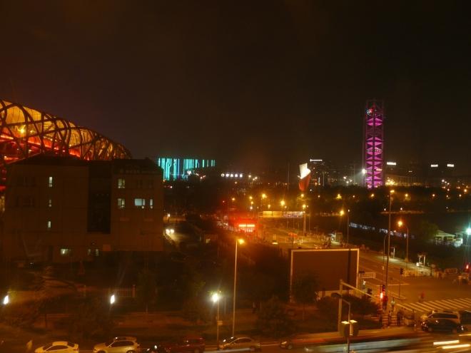 Olympijský areál v noci (vlevo stadion, vpravo rozhledna měnící barvu).