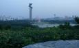 Výhled na Peking z balvanu na vrcholu kopečku v parku. Monstrózní rozhledna stále vévodí.