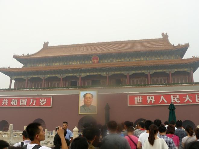 Vstupní brána do Zakázaného města, resp. trojbrána, protože jí vedou tři tunely. Později se ukázalo, že jde teprve o první vstupní bránu. Dovnitř se všemi třemi tunely valí spousty Číňanů, na něž neustále hledí obrovský Mao Ce-tung.