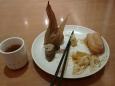Snídaně na hotelu. Vlevo malý šálek černého čaje, na talíři zleva kukuřice plněná rýží a ještě asi něčím, čínské hůlky, jakási směs zeleniny a nejlepší napodobenina pečiva, jen trochu mastnější.