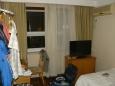 """Hotelový pokoj byl zařízený naštěstí dost evropsky (či americky), byť jsem v něm po příchodu z venku někdy cítil zvláštní vůni, kterou jsem ještě nezažil (podobnou vůni jsem ale cítil i jinde, třeba v nákupním centru.). Pokoj byl akorát tak velký, mimo jiné s širokou postelí, psacím a nočním stolkem a nezbytnou klimatizací. Přebývala v něm jen televize. Vedle se nacházela koupelna se záchodem """"amerického"""" typu: delší mísa a jiný způsob splachování (vcucnutím vody)."""
