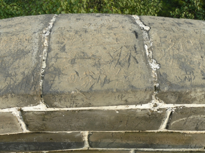 Zeď zblízka s vyškrábanými vzkazy a značkami