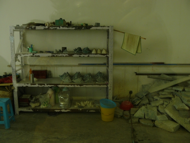 Přes sklo vidíme dílnu sochaře opracovávajícího nefrit.