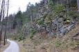 Nad stezkou se zdvihá skalnatý svah Borku.