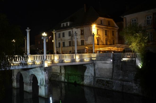 Dál pokračujeme podél Lublaňky směrem zpět k Trojmostí. U řeky je velice příjemná atmosféra, plno zahrádek a bavících se lidí. Zde se ohlížíme za Ševcovským mostem (Čevljarski most), jenž v nějaké podobě překlenuje řeku už od 13. století, nejnovější verzi pak vymyslel – nečekaně – Jože Plečnik.