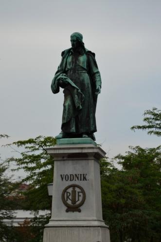 Míjíme Vodnikův památník na Vodnikově náměstí (Vodnikov trg). Valentin Vodnik byl básník, publicista a průkopník slovinského jazyka, žil na přelomu 18. a 19. století.