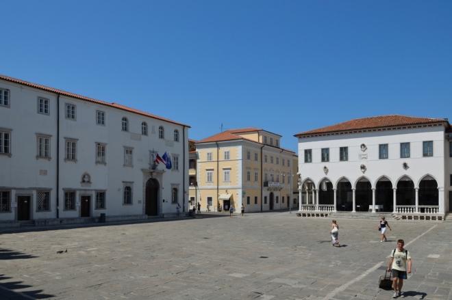 """Titovo náměstí (Titov trg) se nachází přibližně, možná i přesně, na vrcholu bývalého ostrova. Vpravo vidíme palác """"Lodžie"""" (Loža), vlevo pak budovu """"Univerzity Přímoří"""" (Univerza na Primorskem), která má většinu fakult právě zde v Koperu a dalších pobřežních městech."""