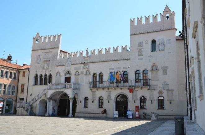 Z jihu uzavírá náměstí Pretoriánský palác z 15. století, jenž spolu s palácem Loža a dalšími budovami ve městě názorně ukazuje, jak vypadá benátská gotika. Branou vlevo jsme sem přišli.