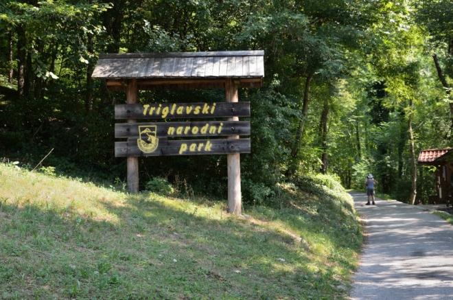 Asi po čtvrthodině chůze nás tato cedule vítá v jediném slovinském národním parku, nazvaném po známém nejvyšším vrcholu Julských Alp, jenž je symbolicky vyobrazen i na státní vlajce a znaku. Vpravo bychom mohli sejít k soutěsce řeky Tolminky, my si ji ale necháme na odpoledne, teď se budeme drápat do kopce po levé straně.