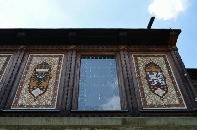 Zvenku jsou po obvodu kostela vyobrazeny znaky zemí rakousko-uherského císařství.