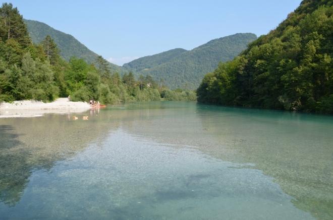 Klasická modrozelená Soča, zleva přitéká Tolminka. Výška hladiny je zde uměle regulována, občas z řeky vystupují ostrůvky, občas vody výrazně přibyde a projede nějaká loď.