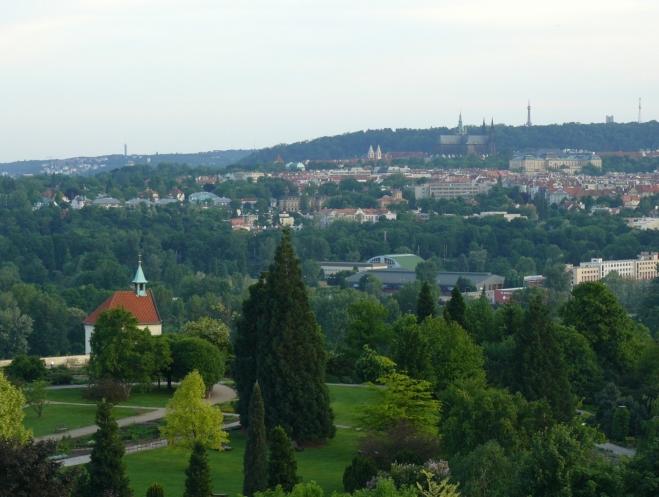 Výhled z botanické: v popředí ornamentální zahrada s kaplí sv. Kláry, v pozadí Stromovka, Pražský hrad a Petřín
