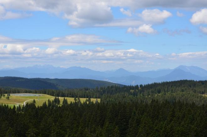 Výhled na západ, až při psaní článku jsem si ujasnil, co jsme zde vlastně viděli. Vlevo je zubatá nejvyšší část Kamnicko-Savinjských Alp v čele s Grintovcem (2558 m), dále vpravo až doprostřed obzoru se pak vypíná trochu nižší východní část stejného pohoří (Velika Raduha má 2062 m). Zbytek obzoru vyplňuje dlouhé hraniční pohoří Karavanky – uprostřed fotky ční špičatá Govca (1929 m), další výrazná špička je úplně vpravo (Uršlja gora, 1699 m), hned za ní se tyčí Peca (2126 m).