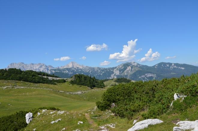 Končíme na vrchu ve výšce kolem 1620 m. Gradišče je náhodou přímo před námi (ten zelený pahorek vlevo), my to ale nevíme. V pozadí východní polovina hlavního hřebene Kamnicko-Savinjských Alp s vrcholy Planjava (2394 m, zcela vlevo), Ojstrica (2350, špička) a Dleskovec (1966 m, zcela vpravo), vrcholy pod největším mrakem se mi nepovedlo jednoznačně pojmenovat.