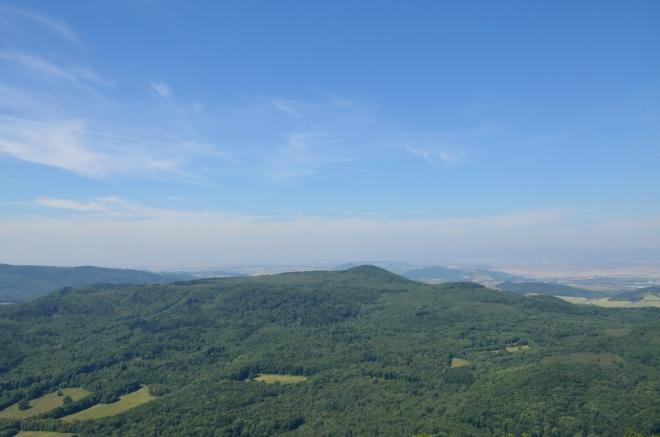 Začínáme na západní straně, zde krajině vládnou lesy. Uprostřed fotky je patrně Pařez, třetí nejvyšší vrchol Českého středohoří (736 m).