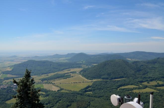 Pohled na jihozápad, v popředí vpravo Milešovský Kloc (674 m) a vlevo Medvědický vrch (též Lhota, 571 m), mezi nimi více vzadu ční Lipská hora (689 m). Informační tabule říká, že v dálce by mohla být nepatrně vidět i Šumava, teď nám ale obzor kvůli oparu končí na 30 až 40 kilometrech.