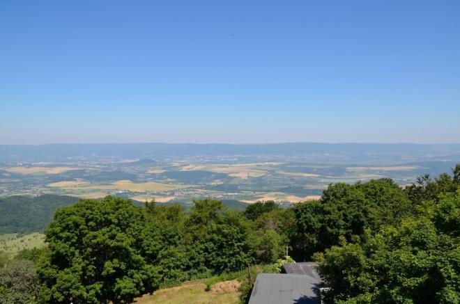 Na severu je k vidění hradba Krušných hor a Podkrušnohorská pánev, po levé straně Teplice.