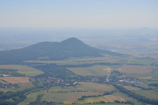 Přiblížení Lovoše, před ním se nachází vesnice Velemín, odkud bychom měli odpoledne odjet zpátky do Prahy. Bílá čára za Velemínem je dálniční most v rámci rozbudovaného úseku D8, která jinak končí vpravo od Lovoše.