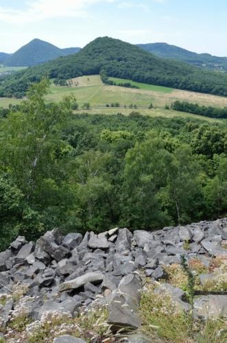 Výhled na sousední vrch Lhota a silnici, po níž bychom sem museli jít, kdybychom neměli alternativní trasu. V popředí opět spousta kamenů, takto vypadají všechny svahy obrácené k západu až severu.