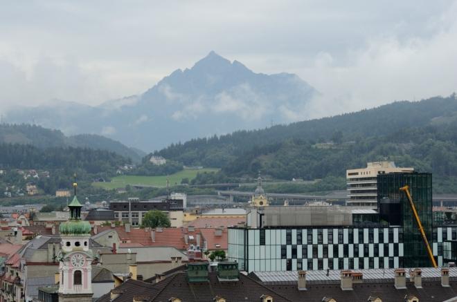 Opodál se z mraků vynořuje rozeklaný vrchol Serles (2717 m), vzdálený asi 16 km.