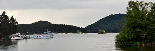 Máchovo jezero z mostu na poloostrov. Les a pobřeží u Doks jsou protkány množstvím asfaltových cest.