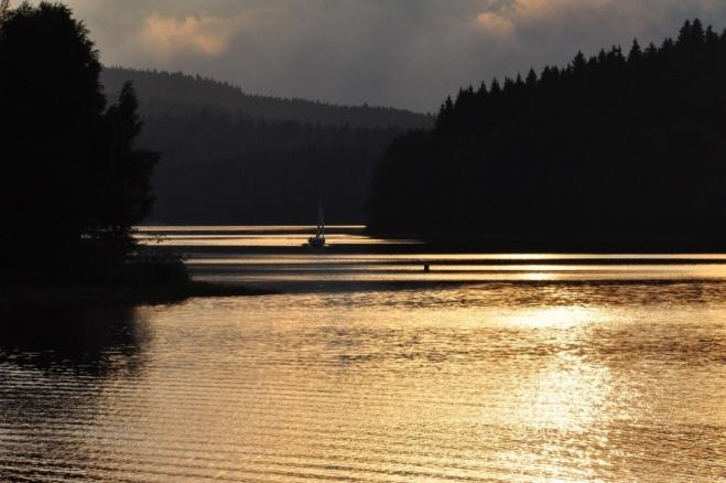 Soumrak mění krajinu a pokrývá vodu zlatem.