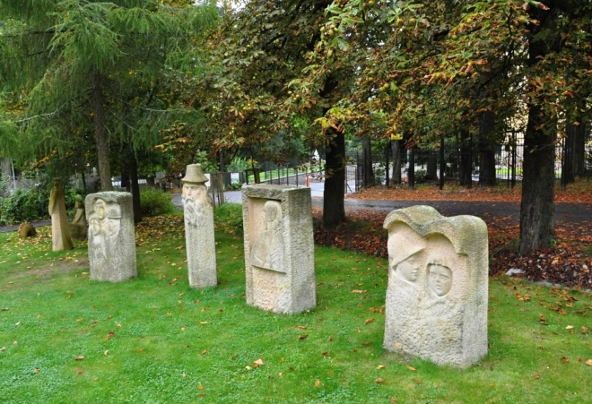 Nedaleko Boheminia stojí hotel Krakonoš a před ním několik dřevěných soch.