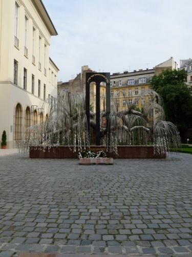 Budovu obhlížíme pouze zvenku, což je asi škoda, soudě podle trojrozměrných záznamů interiéru na internetu. Zadní branou je vidět například tento památník v podobě smuteční vrby, jenž připomíná maďarské židy zavražděné nacisty (těchto obětí bylo nejméně 400 tisíc).