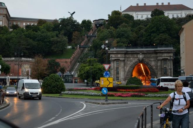 V Budíně nás vítá rušná křižovatka, do každého záběru se nevhodně připlétá aspoň jedno auto a aspoň jeden člověk. Jak sami vidíte, Hradní vrch se dá podjet tunelem a nahoru vede mimo jiné i lanovka.