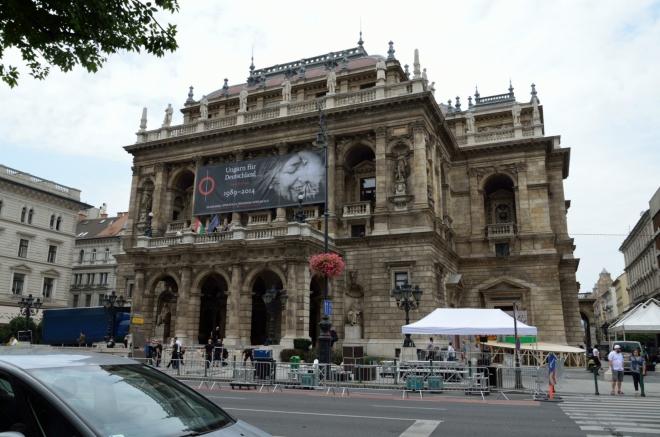 Široká Andrássyho třída je po uličkách, kam se sotva vejde chodník, docela příjemná změna. Zde stojíme před novorenesanční budovou Maďarské státní opery (Magyar Állami Operaház), jež byla otevřena roku 1884 a jež shora, až na červenou střechu, připomíná pražské Národní divadlo. Pořídit slušnější fotku je problém, neboť se tu zrovna staví nějaké pódium, dělníci mi do záběrů zákeřně vztyčují nosníky.