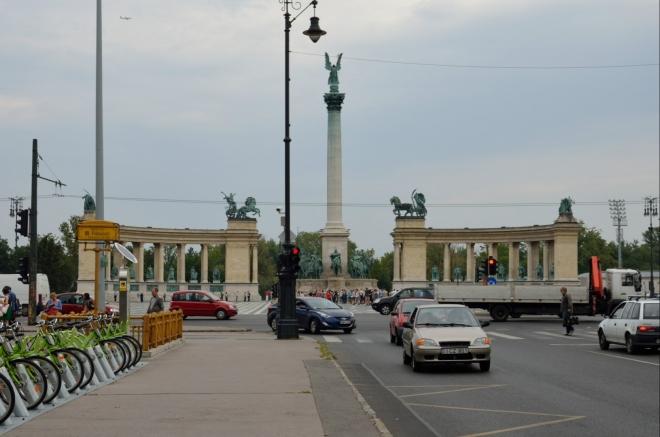 """Třídu uzavírá velkolepě pojaté náměstí Hrdinů (Hősök tere/""""hőšök tere"""", přehláska tvořená čárkami se čte dlouze), dokončené roku 1929. Jeho ústředním bodem je Památník tisíciletí (Millenniumi emlékmű, opět oslava kulatého výročí Uher), připomínající zejména významné vůdce a hrdiny z maďarské historie."""