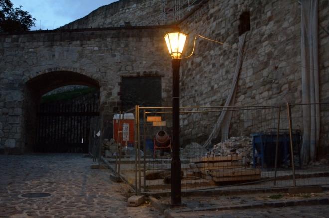 Hrad už je samozřejmě zavřený, můžeme si ho nanejvýš obejít zvenku. Zde jsme u hlavní brány, romantiku středověké stavby podtrhuje míchačka a přenosná toaleta.