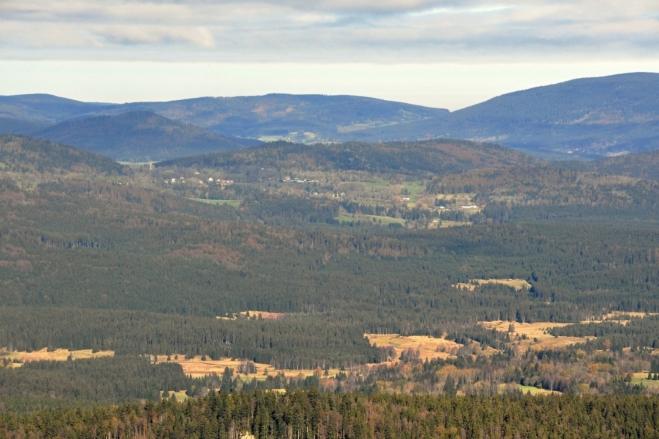 Nad Novým Údolím dohlédneme k domkům Českých Žlebů, Radvanovickému hřbetu. Vzadu je Obrovec a kus Boubína.