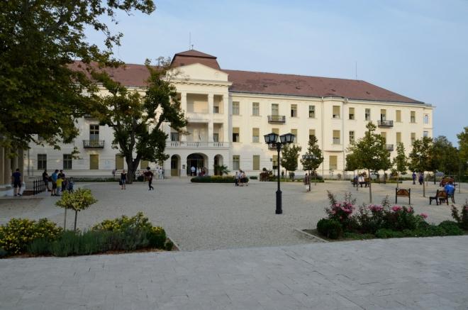 """Hlavní náměstí nese název Gyógy tér (""""ďóď tér""""), což znamená """"Léčebné náměstí"""" či něco podobného. Pozadí vyplňuje místní kardiologická nemocnice, největší svého druhu v Maďarsku."""