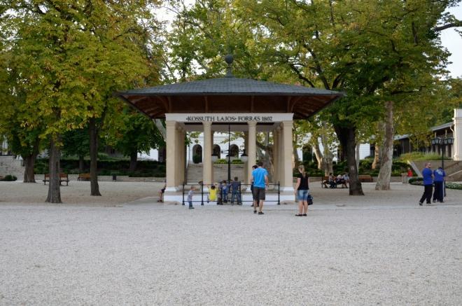 """Ústředním bodem náměstí je klasicistní """"přístřešek"""" (snad altán) nad Kossuthovým (""""košútovým"""") pramenem."""