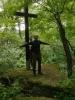 Kříž na skalce v zarostlém svahu nad červenou značkou