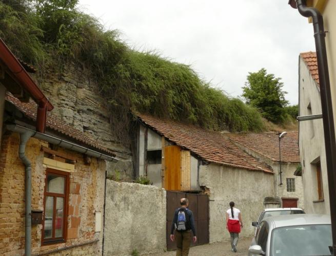 V bývalém hradním příkopu vede ulice okolo hradu s domky nalepenými na jedné straně na skálu, na druhé straně na zříceninu.