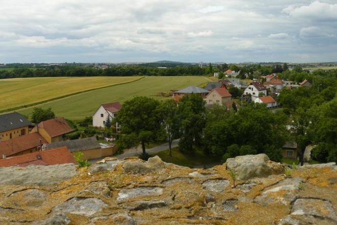 Pohled z věže k Praze, (maličké) paneláky uprostřed tvoří sídliště Ďáblice, nad nímž se tyčí kopec Ládví (uprostřed)