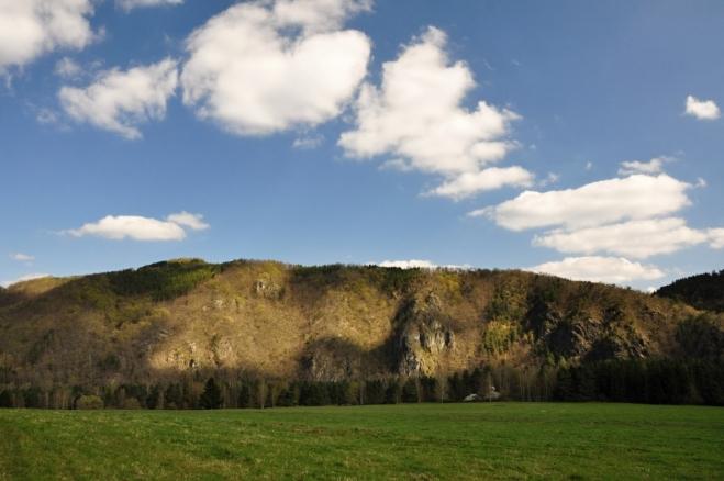 Zelená značka nově nesleduje břeh Vltavy, ale vystupuje na hřeben Varty s výhledem na skály Podkovy.