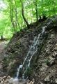Vodopád odhaluje strmost okolních svahů. Les kolem je svěže zelený a je pohoda jím procházet.