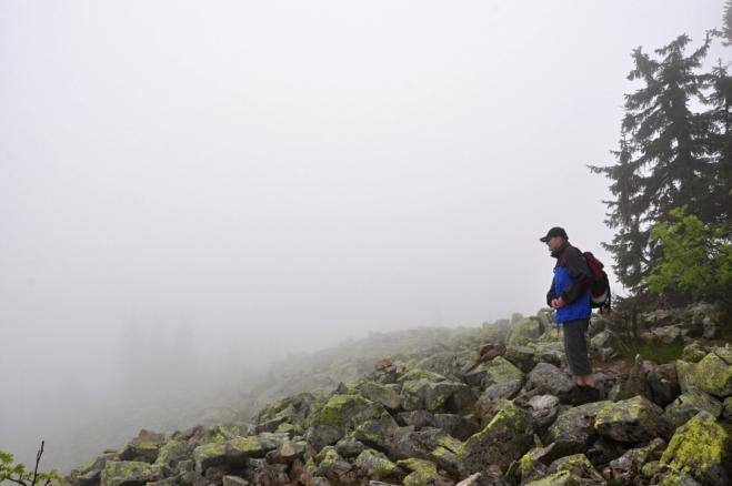 Roman vyhlíží horskou chatu. Ta je nedaleko utopena v mlhách.