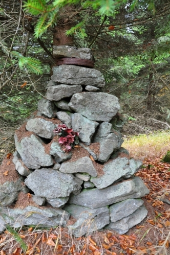 Vrcholová pyramida je vlastně hrobem psa, mazlíčka zdejších chalupářů či obyvatel. Pod vrchním kamenem skrýva v rezavé plechové krabici letitou vrcholovou knihu.