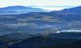 Kleť (1 084 m n. m.),  v pozadí Novohradské hory.