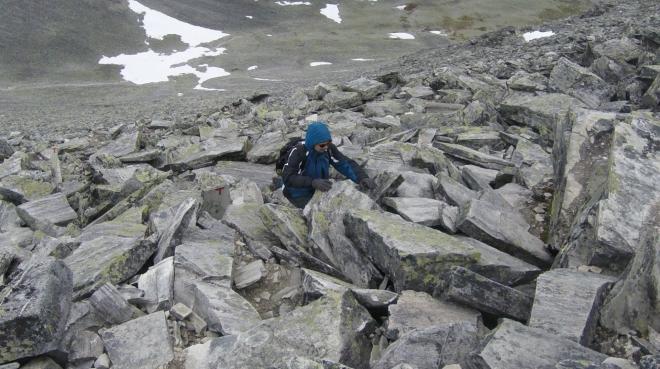 Od sedla stoupáme velice zajímavým terénem plným deskovitých skal a obrovských kamenných schodů (samozřejmě přírodních). Dostat se tímto terénem dolů bude ještě větší legrace než výstup (ačkoliv už teď mnohdy zapojujeme všechny končetiny).