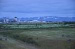Pohled na zasněžené hory v dáli, v popředí se pasou kachny či husy.