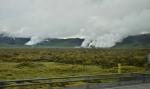 Cestou z autobusu pozorujeme lávová pole a za nimi (zřejmě) geotermální elektrárny.